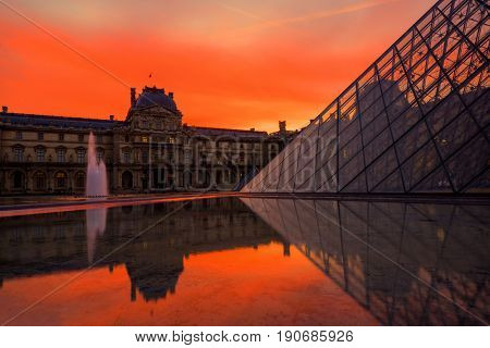 PARIS, FRANCE - DECEMBER 9, 2017: View of famous Louvre Museum with Louvre Pyramid at evening. Louvre Museum is one of the largest and most visited museums worldwide
