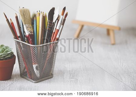 Fashion Artist Table Desk. Creative Workspace With Paint Brushes, Pencils, Succulent And Canvas On E