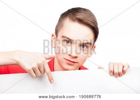 Cute teenager boy wearing red polo shirt  pointing his finger on blank white board or banner. Isolated on white background