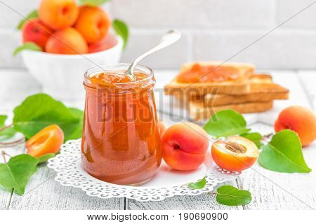Apricot jam in a jar and fresh fruits with leaves on white wooden table breakfast