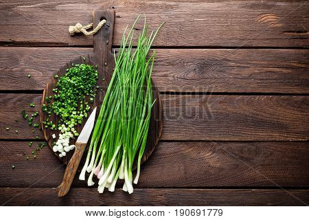 Green onion or scallion on wooden board fresh spring chives