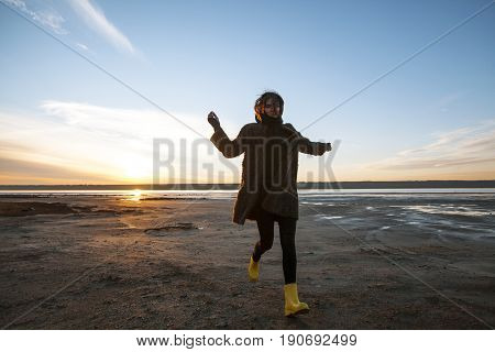 Beautiful girl in a coat walks on the lake in winter, beautiful sunset,sun rays,casual outfit,sundown,cold,autumn,pretty,attractive,stylish wear,curly hair