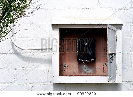 Old electric box on the side of an abandoned warehouse.