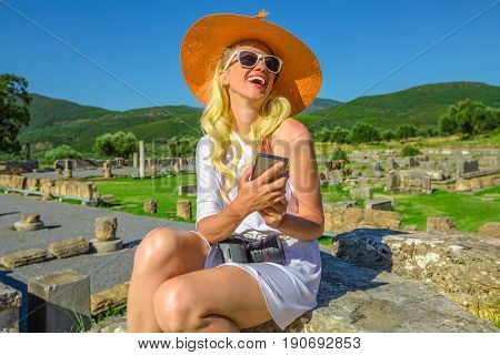Blonde caucasian woman holding smart phone enjoying in Ancient Messene stairs Historical Site in Peloponnese, Greece, Europe. Seductive tourist in greek dress and sun hat sitting on ruins of stadium.