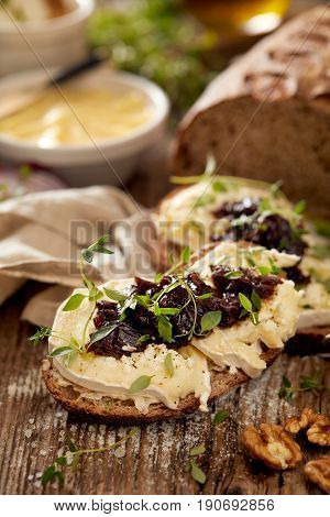 Sandwiches with goat's bread with goat cheese, caramelized red onion and fresh thyme on wooden table