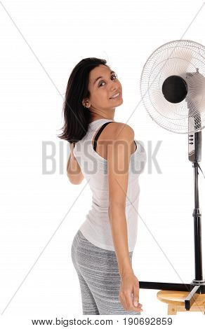 A young Hispanic woman in gray leggings standing in front of a fan to cool up from the heat isolated for white background.