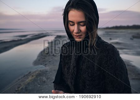 Beautiful girl in a coat walks on the lake in winter and see to the sundown