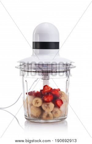 Electric Blender filled with different fruits isolated on white background