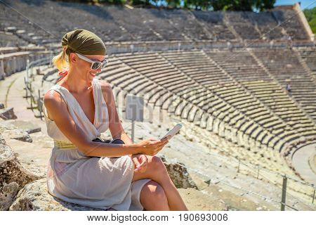 Smiling woman looking at smart phone on stairs of Ancient Theater Epidaurus in Peloponnese, Greece, Europe. Mediterranean travel destination enjoying. Epidaurus amphitheater is a famous greek heritage