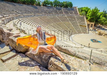 Epidaurus amphitheater. Smiling woman with orange sarong and greek clothes enjoying at Ancient Theatre Epidaurus, Peloponnese, Greece. European travel destination. Historical heritage and landmarks.