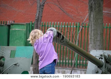 Kharkiv - April 11: Girl Masha Alexandrova shoved her hand into the trunk of a battle cannon at the site of the historical museum on April 11 2004 in Kharkov Ukraine.