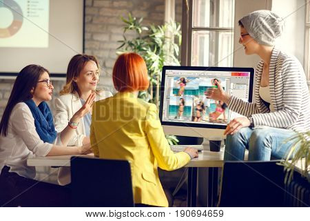 Young female graphics designers agreeing about design of front page of magazine