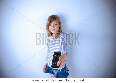 Young girl pointing with the TV or video remote control and pushing the power button