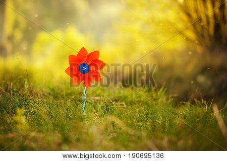 One orange pinwheel against nature background in sunny summer day.
