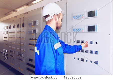 Engineer presses the red button on the control panel of power plant. Adjustment of industrial control systems for specialists in helmets. Cabinet with controllers and terminals of relay and automation