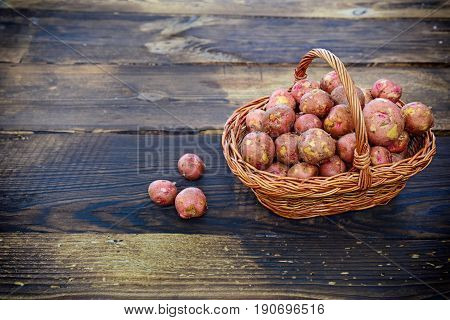 Raw potatoes in a wicker basket on a brown wood background top view