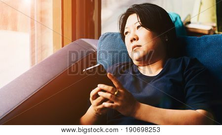 Asia Women 40S Holding Smartphone Thinking On Sofa