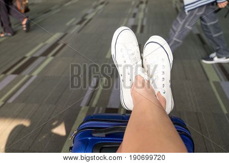 Close up cross leg wear white sneaker lay on suitcase at airport terminalTravel Vacation concept.