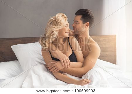 Young couple man and woman intimate relationship on bed hugging