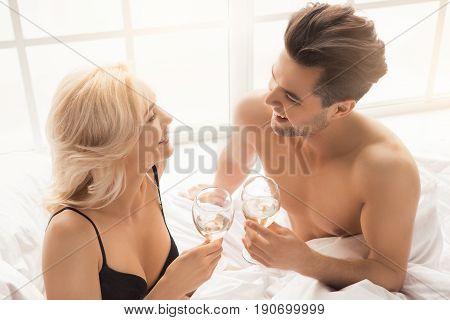 Young couple man and woman intimate relationship on bed drinking champagne
