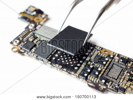 Close-up image of technician replacing flash storage (NAND) of smartphone motherboard