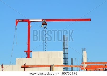 Small mini hoisting crane for multipurpose use in construction sites especially for masonry from large format silicate blocks and sandstone blocks; photo from building a house