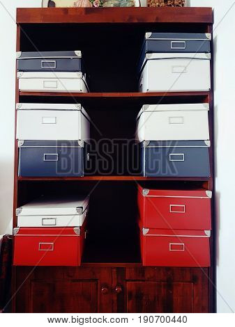 Variety of paper storage boxes in different sizes and colours stacked in a row on wooden book shelves for organisation and convenience