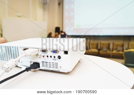Modern technology, a white projector on the table prepared to broadcast video presentations on a large screen in the audience. Organization and conduct of training events.