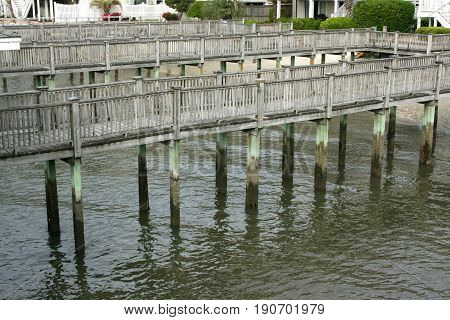 A walkway of docks weaving back and forth sitting high above the water with no boats docked.