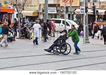 JERUSALEM, ISRAEL - DECEMBER 29, 2016: A young man helps to move in a wheelchair to an orthodox Jew in front of the Mahane Yehuda market in Jerusalem