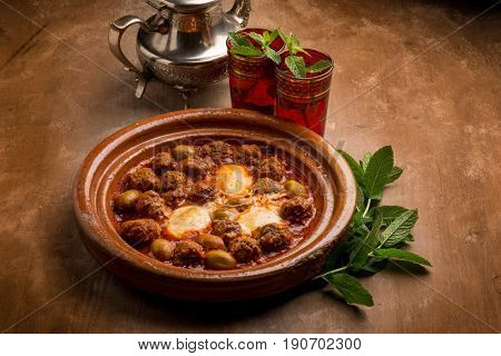 tajine with meat balls eggs green olives and tomato sauce