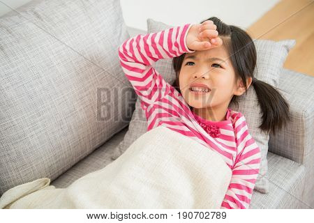 Sick Child Girl Lying Down On Sofa With Fever