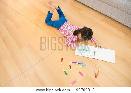 Children Lying Down Near Sketchbooks