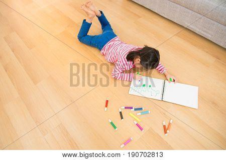 Children Lying Down Near Sketchbooks