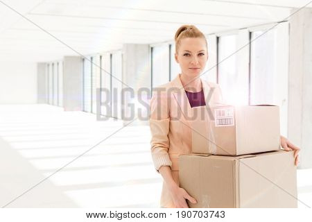 Portrait of young businesswoman carrying cardboard boxes in new office