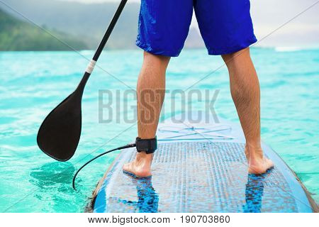 Paddle board man doing stand-up paddleboard on ocean. Athlete paddleboarding on SUP surf board on Hawaii beach travel. Closeup of legs standing on board.