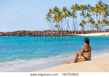 Hawaii beach travel tropical getaway bikini girl on Big island. Hawaiian tropical nature landscape with palm trees and volcanic beach in background.