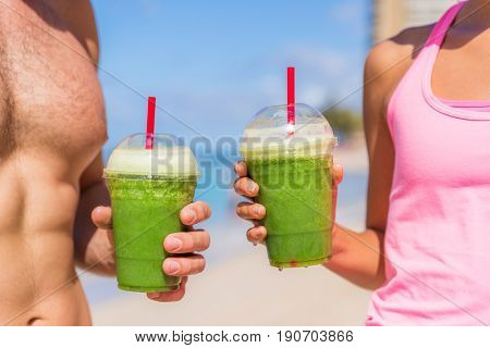 Green smoothie fit fitness healthy people drinking juice at exercise workout. Closeup of couple hands holding detox drink outdoors.