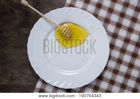 White plate with honey on a wooden table