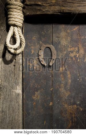 Rusty horseshoe and rope on an old wooden door