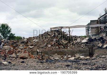 Destroyed the factory building and the road as after shelling. The mountain of debris