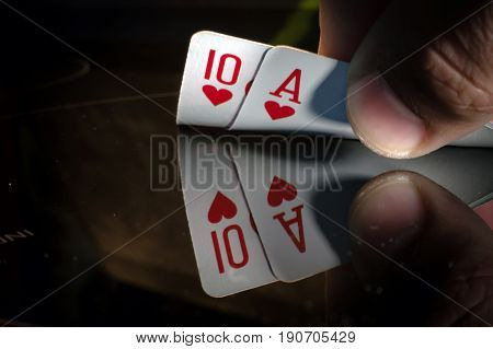 a ten and an ACE of spade in the hands of the player in blackjack or poker but a black background