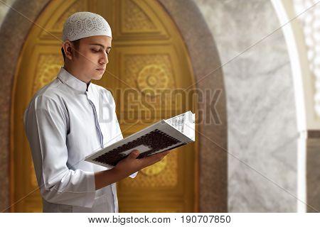 Asian muslim man reading koran in mosque