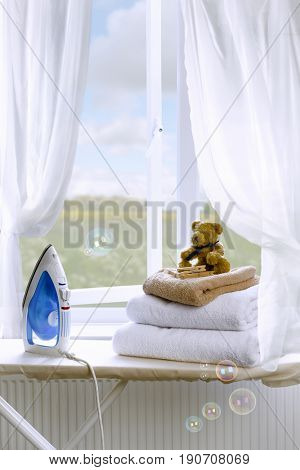 Freshly laundered towels on an ironing board with iron