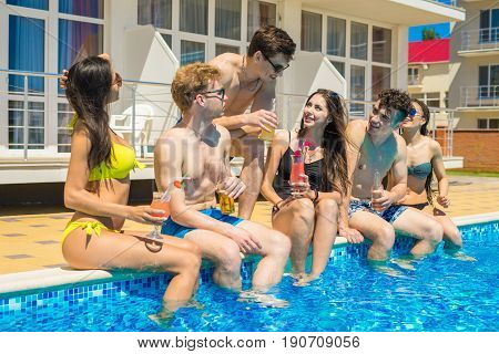 Party at smimming pool. Group of cheerful friends drinking cocktails and beer sitting on the edge of the pool. They look happy