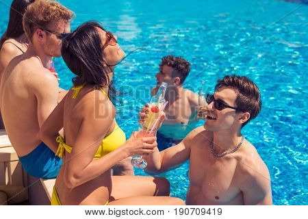 Party at smimming pool. Group of cheerful couples drinking cocktails in the pool. pickup Guy tries to meet a girl
