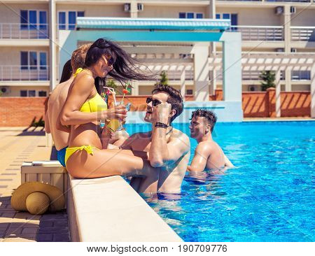 Party at smimming pool. Group of cheerful couples drinking cocktails in the pool. pickuper Guy tries to meet a girl