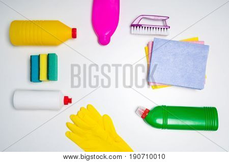 Range of cleaning products for the kitchen and bath. Detergents, chemical bottles, cleaning sponges and gloves. On a wooden table. view from above.