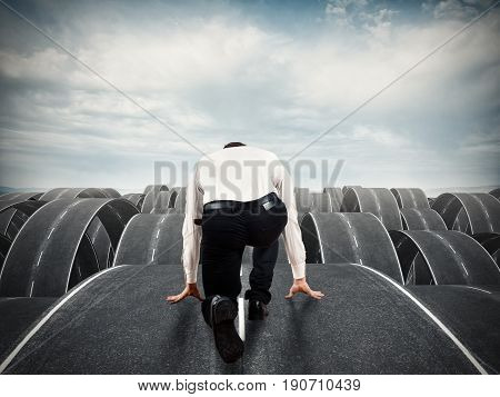 Businessman ready to start on complicated multiple roads. Concept of determination, confusion, decision