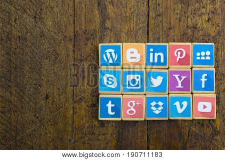 QUEENSTOWN SOUTH AFRICA - 09 APRIL 2017: Social Media logotype popular collection printed and place on wood scrabble game pieces isolated on rustic brown wood planks